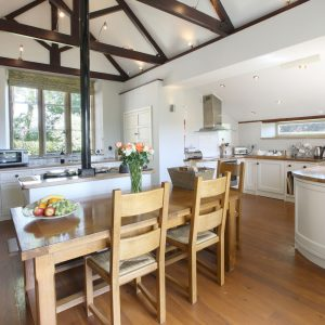 The stunning dining and kitchen area with original wooden beams, and arched church style door at the luxury dog friendly cottages, Dorset, Old School Kitchen