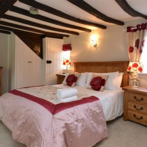 You'll have sweet dreams in this wooden beamed holiday cottage pink themed bedroom in the New Forest