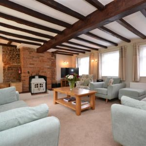 A relaxing lounge with wooden beams at New Forest Holiday Cottages