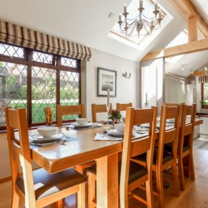 A beautiful dining room with wooden dining table perfect for entertaining all the family whilst staying at a New Forest Holiday Cottage