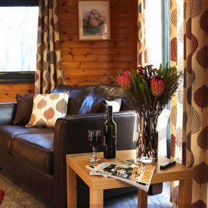 Relaxing living area with wooden floors and leather sofas, perfect for a dog friendly holiday at Flowery Dell Lodges, North Yorkshire