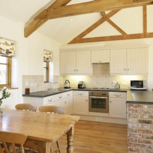 A perfect blend of new and old with this contemporary kitchen featuring wooden beams, wooden floor and stone cladding. Luxury self catering accommodation, Bicester, Oxfordshire.