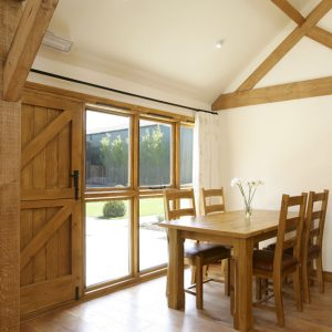 A room with a view - a stylish dining area with feature windows overlooking a holiday cottage garden in Oxfordshire