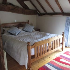 A beamed bedroom ceiling with pine bed at Hipsley Farm holiday cottages, Warwickshire