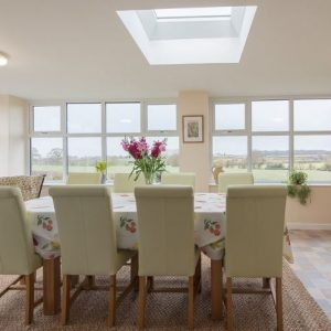 A beautiful conservatory with light and airy windows and sweeping countryside views, all set for dining at Hipsley Farm Self Catering Accommodation, Warwickshire