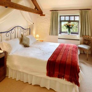 A country bedroom with wooden panelling at Oatridge Holiday Cottages, Forest of Dean