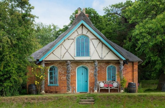 A unique holiday cottage in the UK with turquoise front door and painted windows