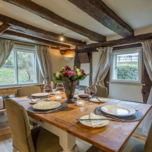 A welcoming dining area with dual aspect windows, wooden flooring and wooden table from Suffolk Hideaways dog friendly holiday cottages