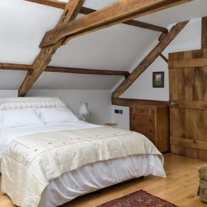A beautiful bedroom with wood furniture, flooring and beams.