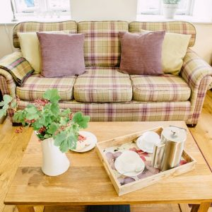 Cosy tartan armchair with cushions and coffee table all set for a refreshing cup of coffee at River Catcher self catering accommodation, Wales