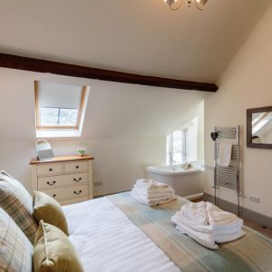 You'll have sweet dreams in this beautiful bedroom with open plan bath from River Catcher holiday cottages in Wales