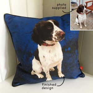 Personalised pet cushion featuring in blue featuring a brown and white spaniel. The picture on the cushion was taken from a photograph.